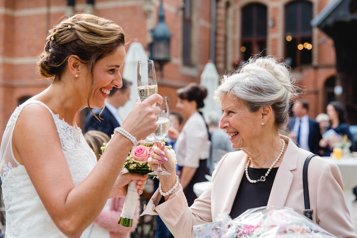 Braut beim Anstoßen mit den Gästen.