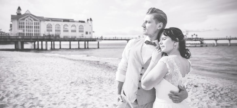 Schwarz weiß Aufnahme eines Brautpaares vor der Seebrücke.