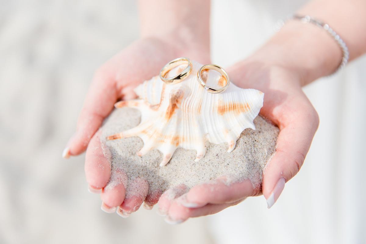 Hochzeitsfotos von Eheringen am Strand.