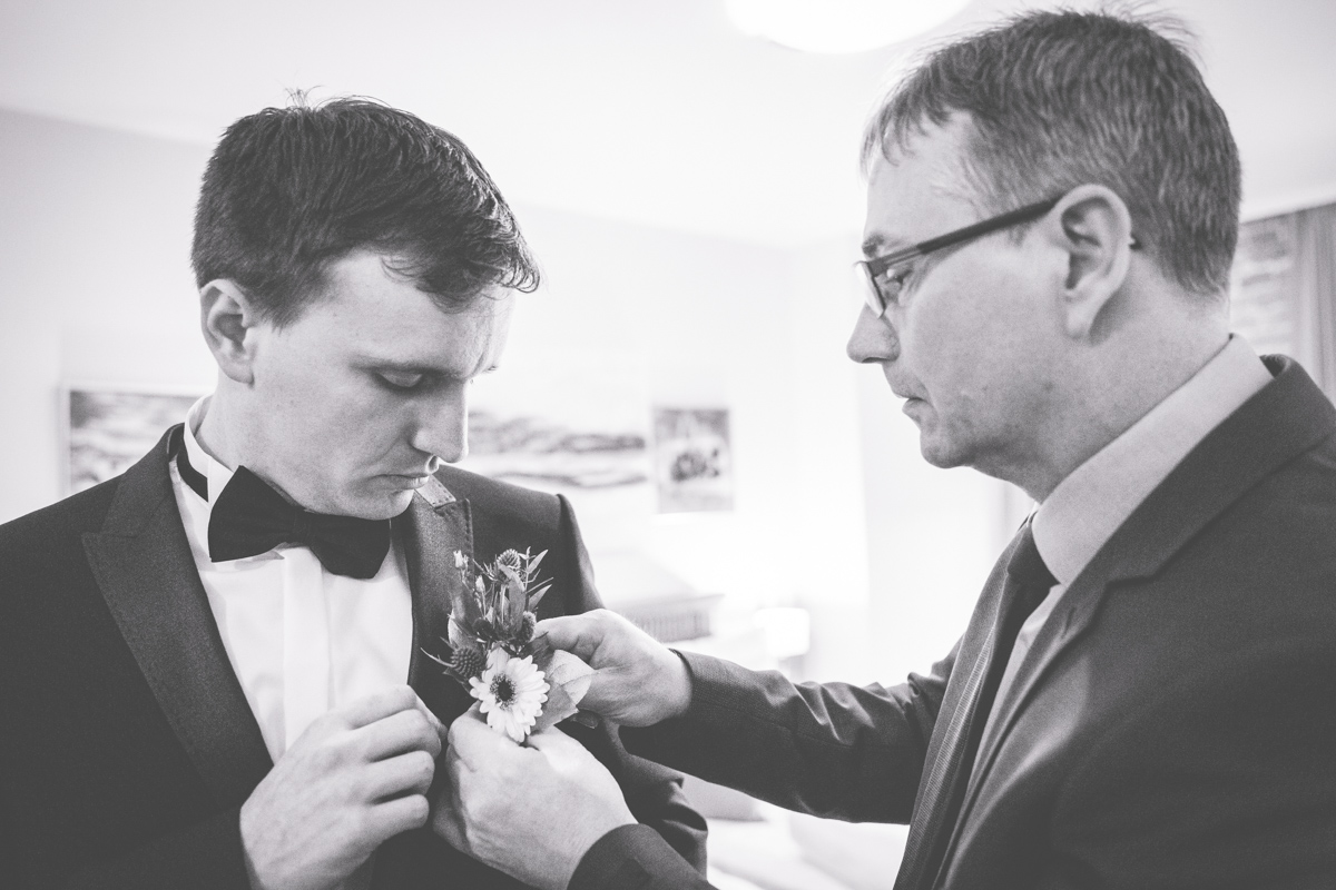 Bräutigam mit Papa beim Anstecken der Blume.