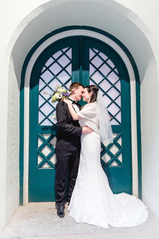 Brautpaar vor einer grünen Tür fotografiert.