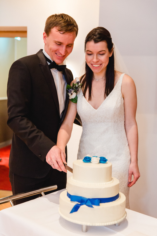 Braut und Bräutigam schneiden die Torte an.