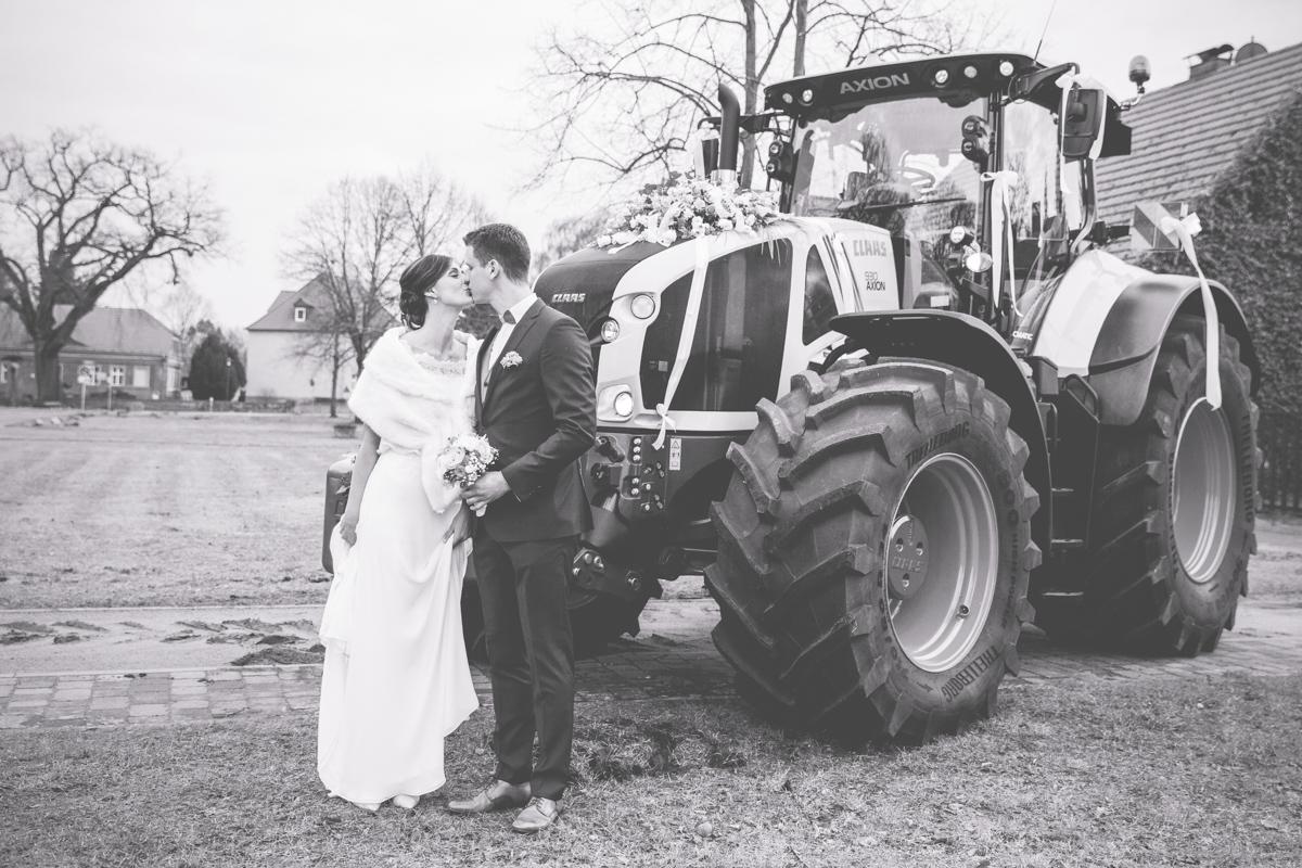 Brautpaar vor ihrem Hochzeitsauto, dem Traktor.