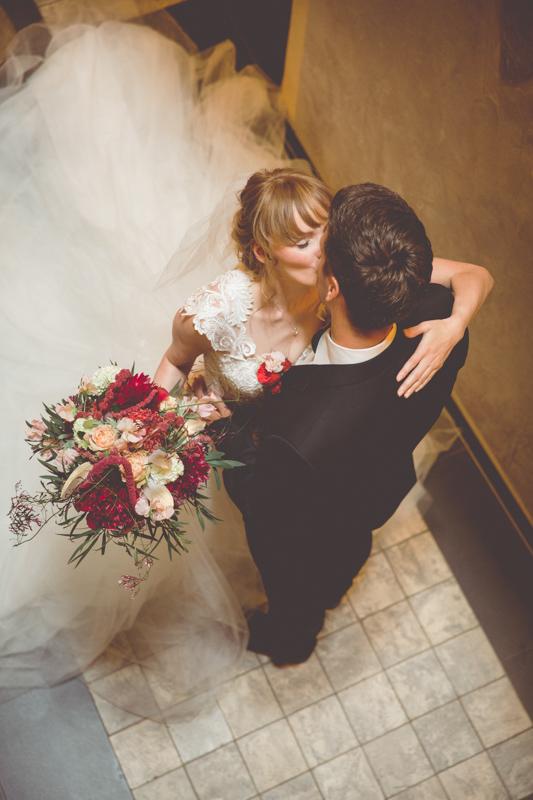 Küssendes Brautpaar im Treppenhaus.