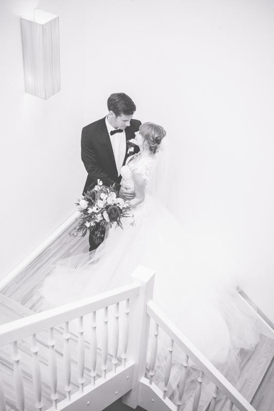 Schwarz weißes Hochzeitsfoto eines Paares im Treppenhaus.