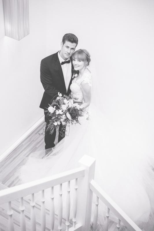 Kuschelndes Brautpaar im Treppenhaus.