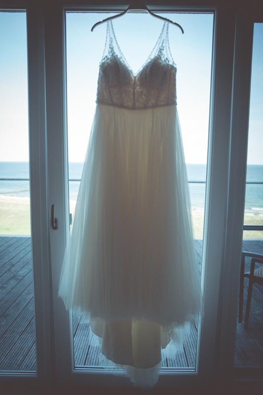 Brautkleid hängt am Fenster, dahinter ist das Meer zu sehen.