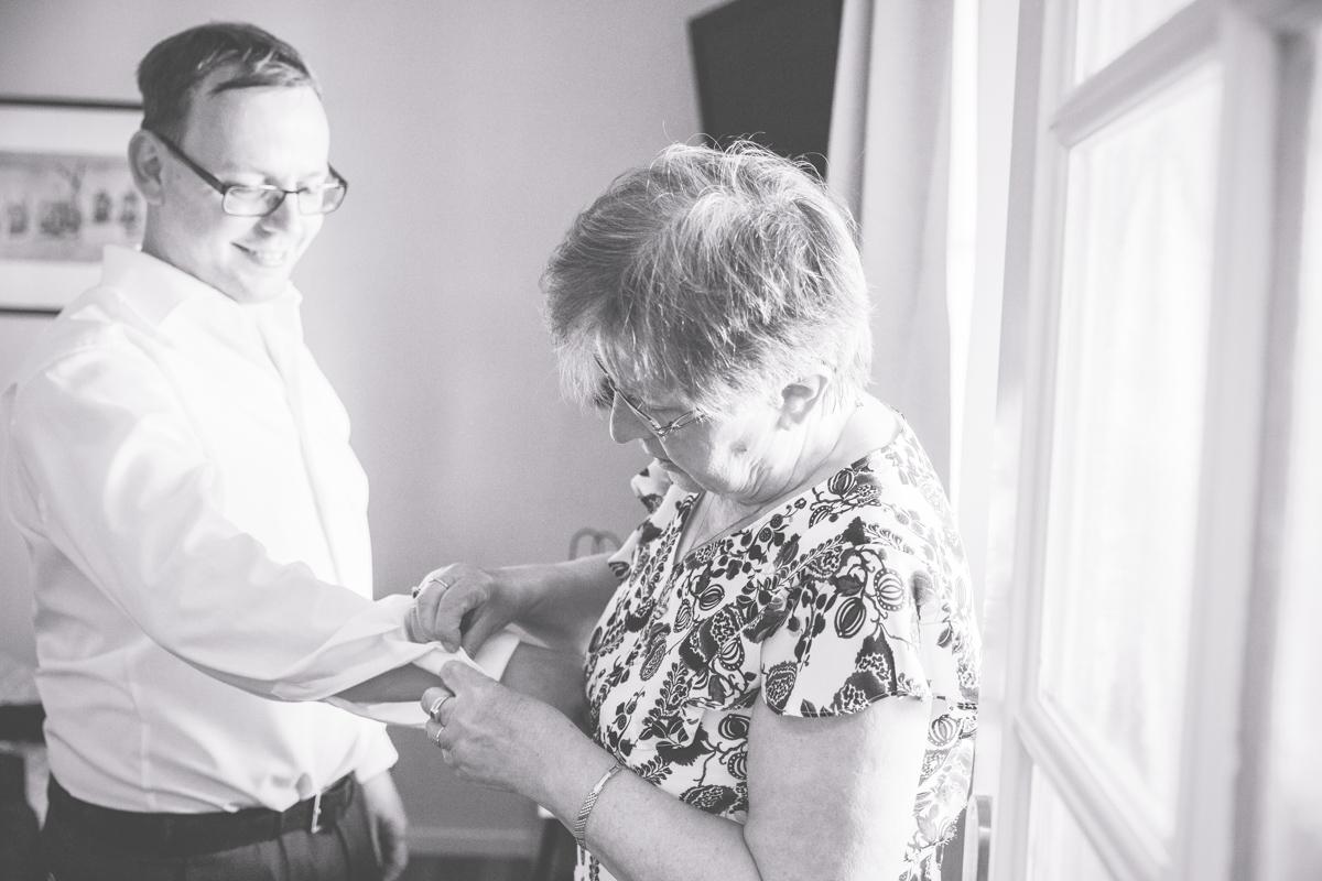 Mama hilft beim Getting Ready des Bräutigams.