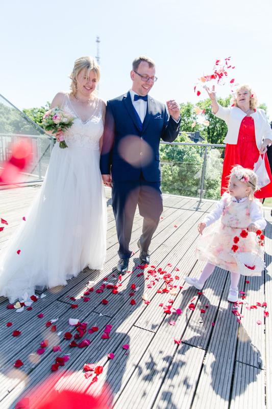 Brautpaar wird mit Blütenblättern beworfen.
