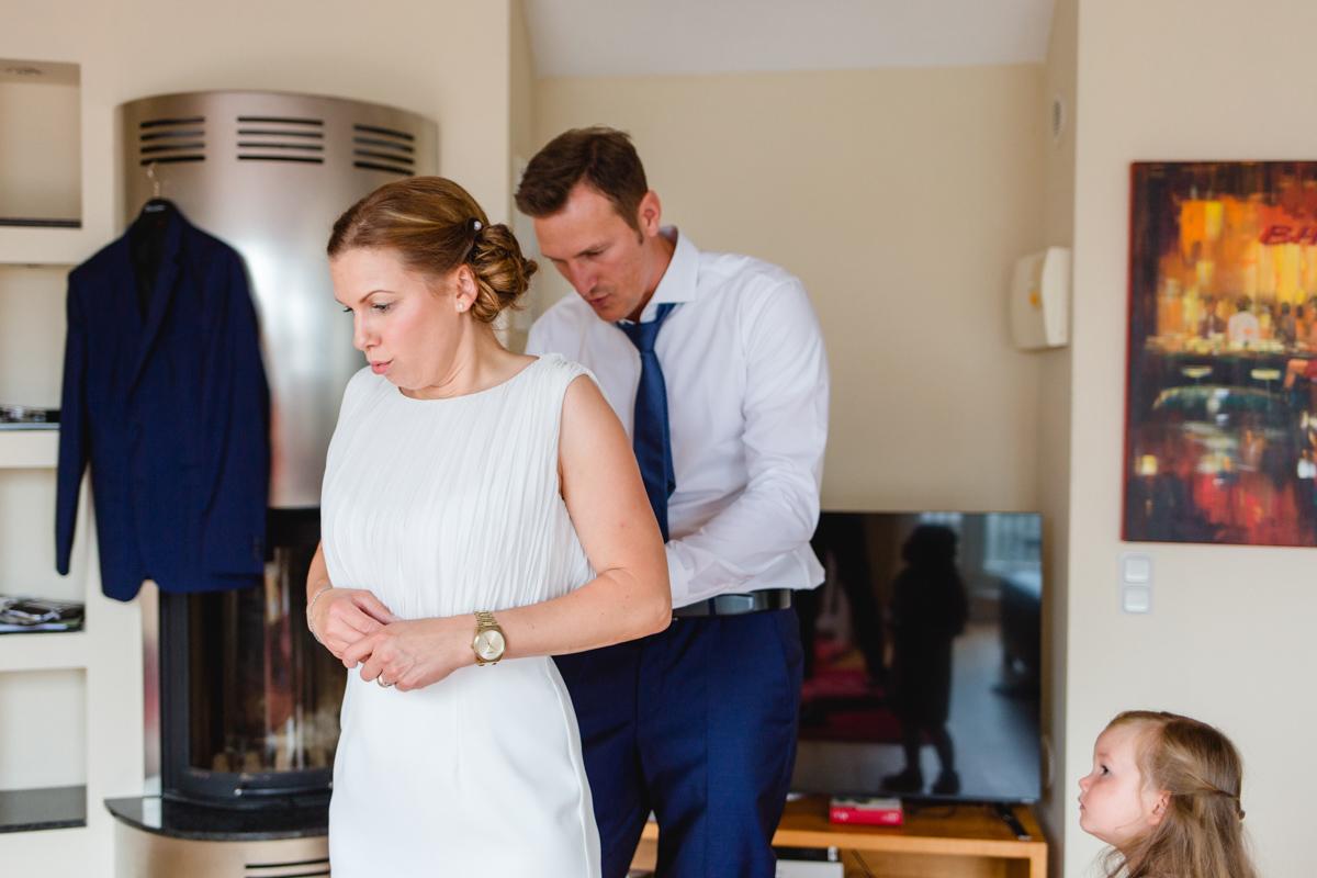 Bräutigam hilft Braut ins Kleid.