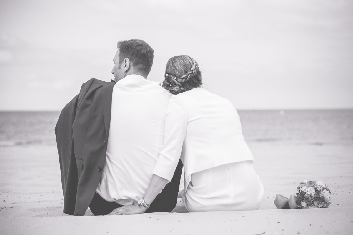 Verliebtes Brautpaar schaut aufs Meer.