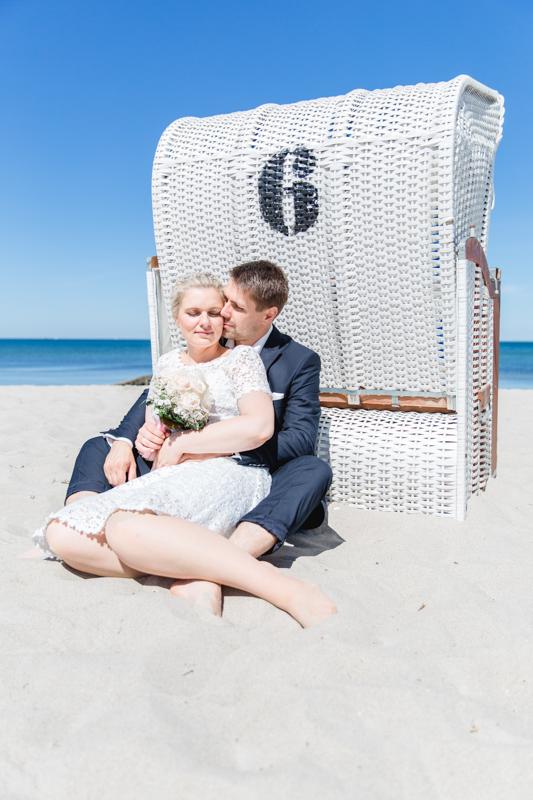 Foto wie sich das Brautpaar an einen Strandkorb anlehnt.