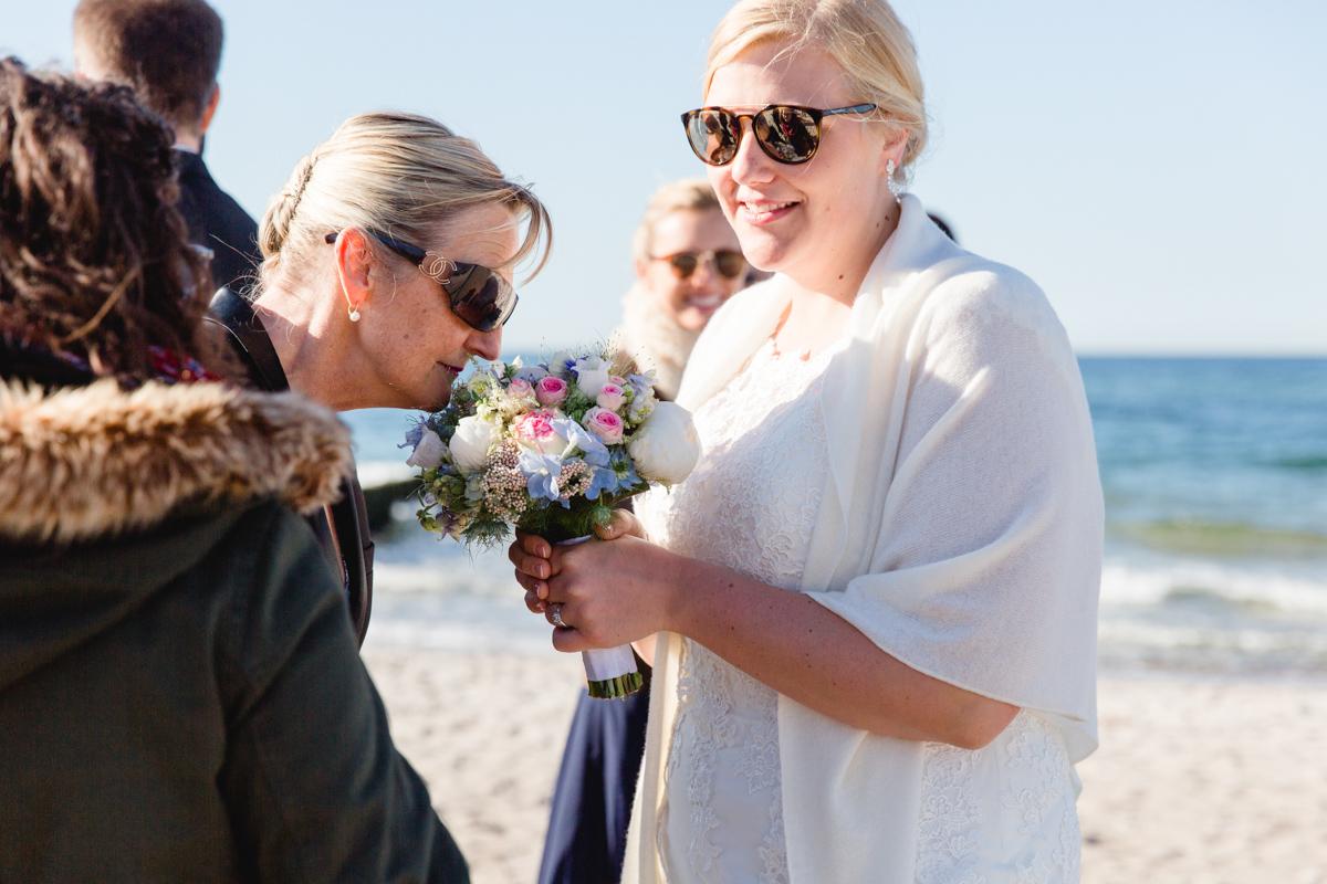 Hochzeitsfoto wie die Brautmutter am Brautstrauß riecht.