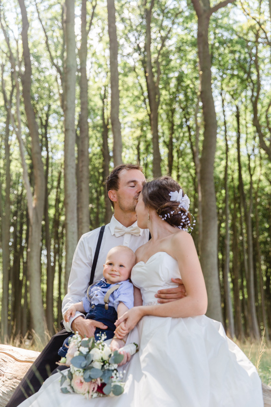 Hochzeitsfotos mit Kind, aufgenommen im Wald.