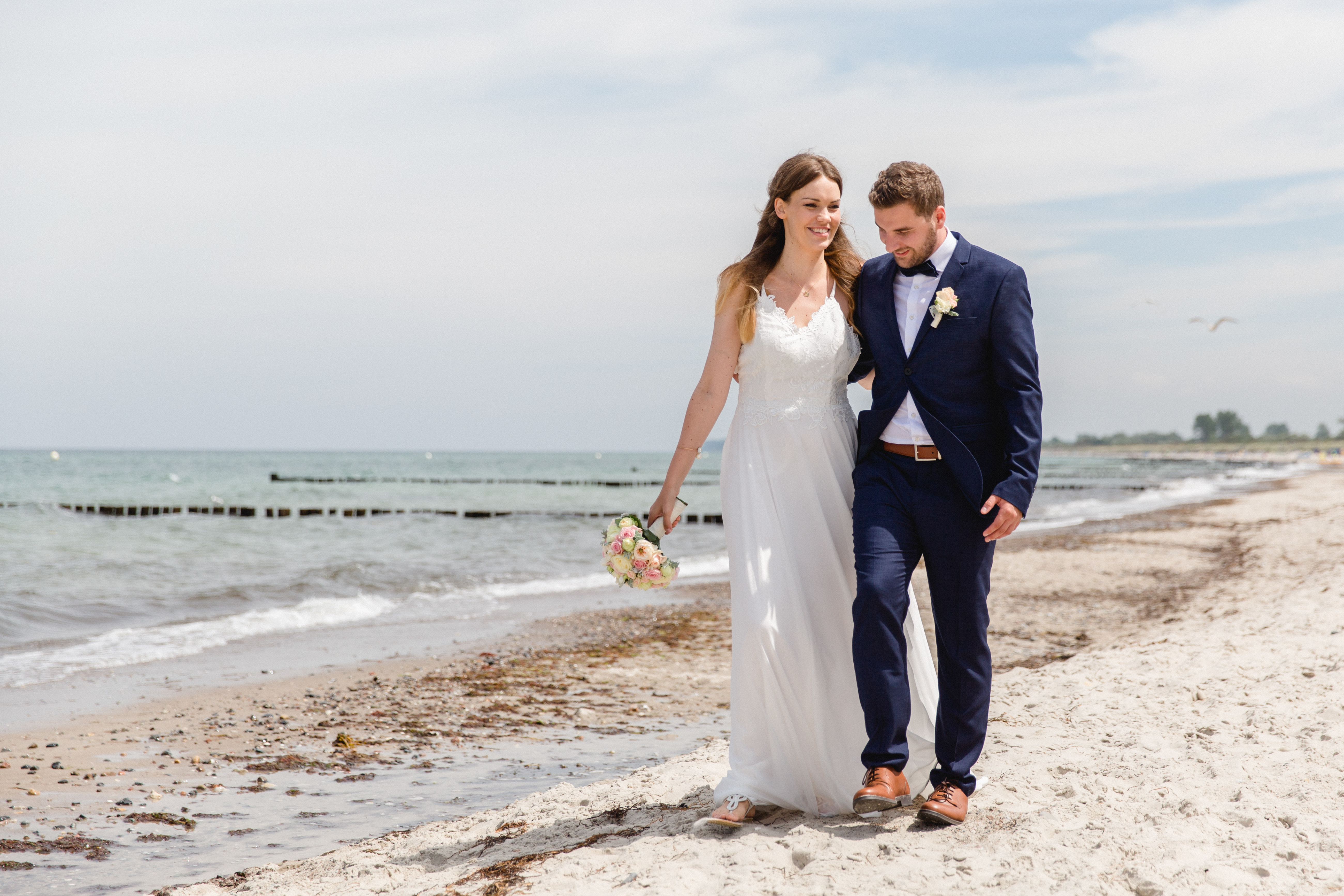 Verliebtes Brautpaar während eines Strandspaziergangs.