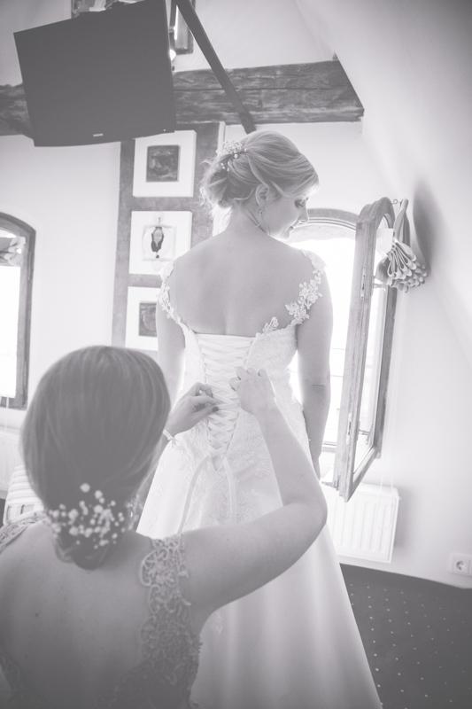 Hochzeitsfoto des Anziehen des Brautkleides.