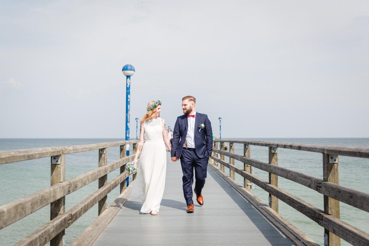Brautpaar läuft die Seebrücke entlang.