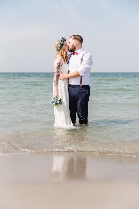 Brautpaar steht beim Shooting in der Ostsee.