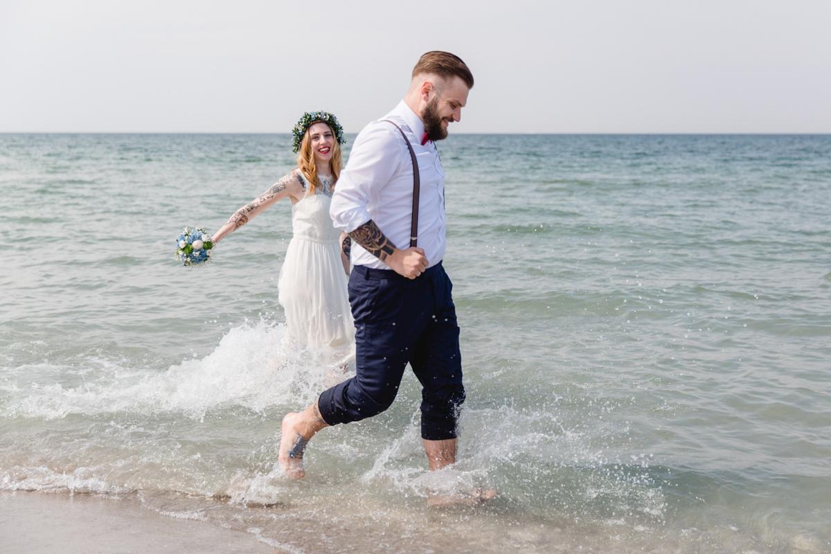 Brautpaar rennt beim Shooting durch die Ostsee.