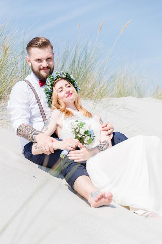 Brautpaar in der Düne sitzend.