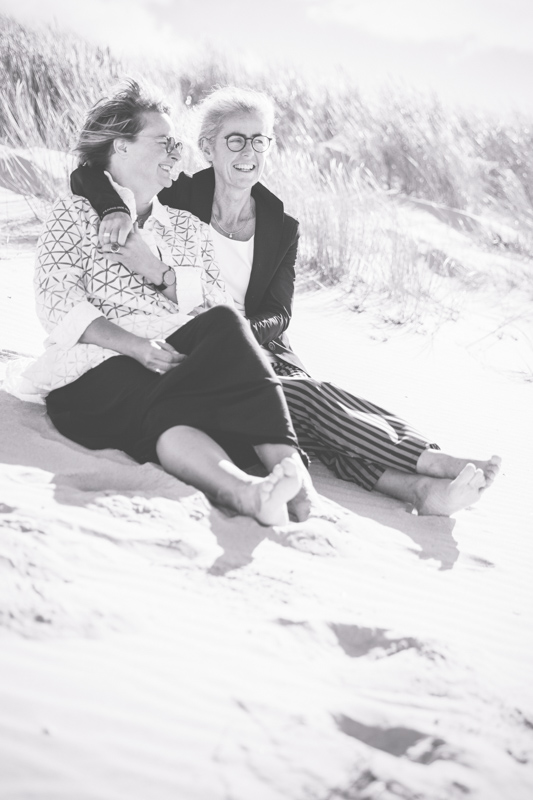 Kuschelnde Frauen am Strand.