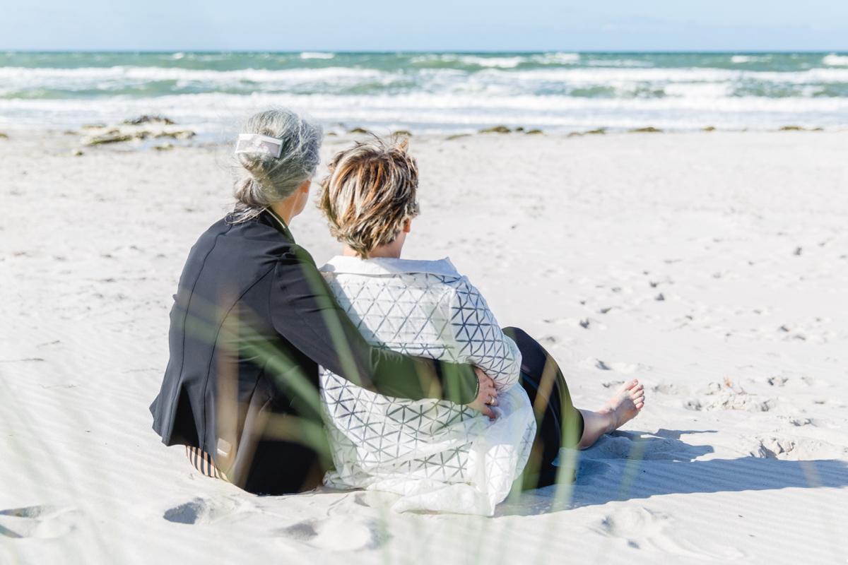 Zwei Frauen nach ihrer Hochzeit am Strand.