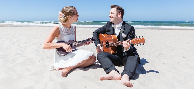 Brautpaar musiziert gemeinsam am Strand von Kühlungsborn.