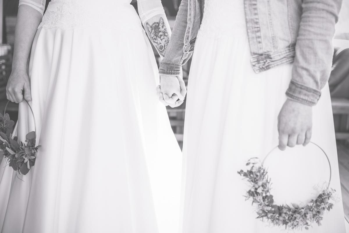 Hand in Hand stehen zwei Bräute vor der Traurednerin.