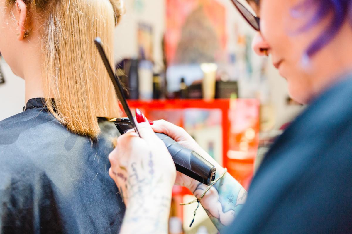 Hochzeitsfoto einer Braut beim Haare schneiden.