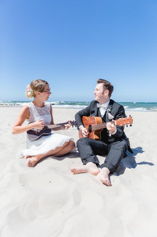 Brautpaar musiziert am Strand mit Ukulele und Gitarre.