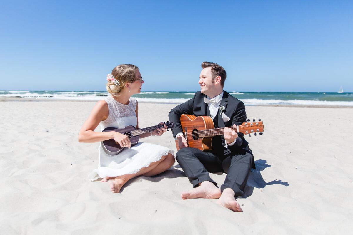 Brautpaar mit Ukulele und Gitarre am Strand.