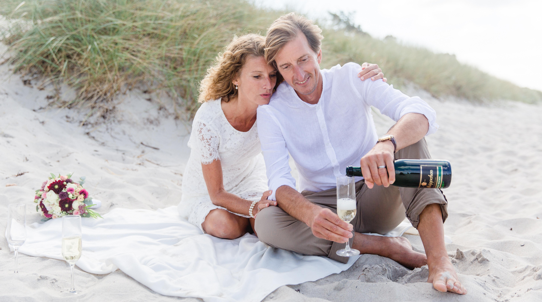 Brautpaar beim Sektempfang am Strand.
