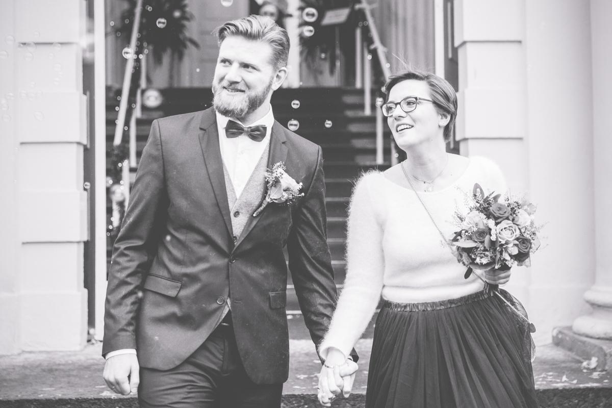 Glückliches Brautpaar beim Auszug aus dem Standesamt.