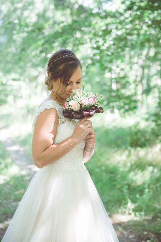 Braut mit Brautstrauß im Wald fotografiert.