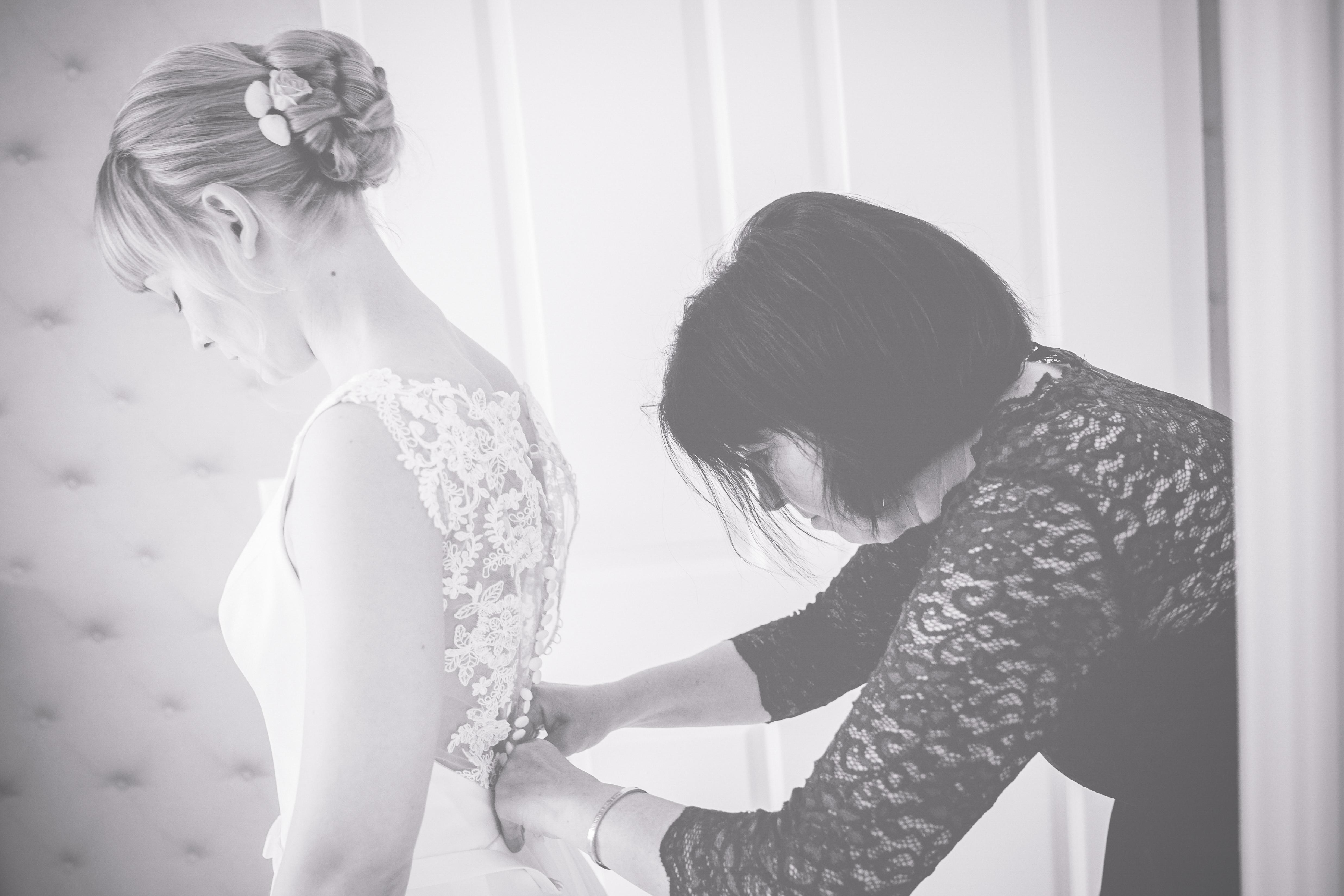 Brautmama hilft der Braut am Hochzeitstag ins Kleid.