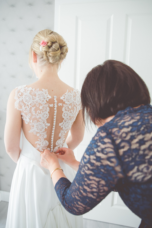 Brautmama schließt das Brautkleid.