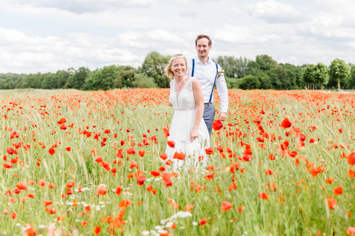 Brautpaar beim Fotoshooting im Mohnfeld.