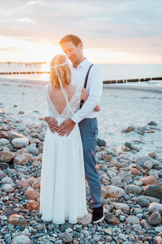 Brautpaar während des Sonnenuntergangs am Strand.