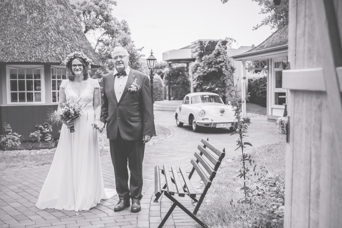 Braut wird von Papa ins Standesamt geführt.