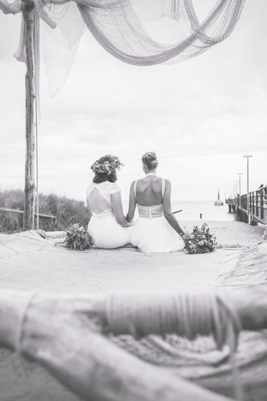 Zwei Bräute beim Fotoshooting am Strand.